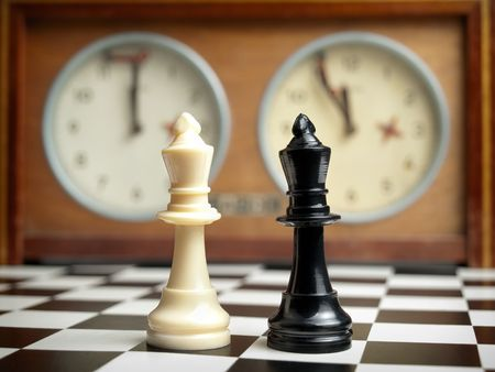 White and black king on the chessboard opposing each other,old chess clock in the background photo