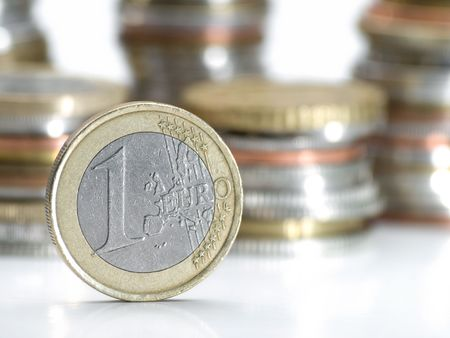 One euro money coin , closeup with stacks of coins in the background, shallow DOF, useful for various economy or financial themes Stock Photo