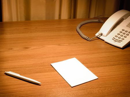 Blank white paper on the wooden working desk with the pen and telephone