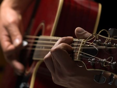 man playing acoustic guitar,shallow DOF, useful for various music and entertainment themes