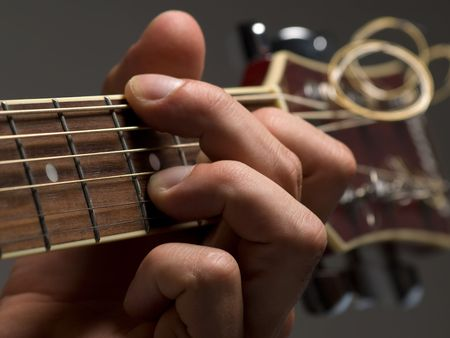 man playing chord on the acoustic guitar,shallow DOF, useful for various music and entertainment themes