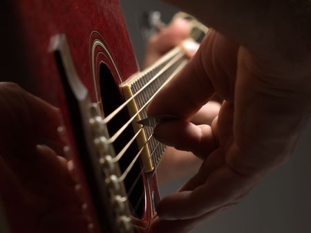 playing the acoustic guitar,selective focus , shallow DOF, useful for various music and entertainment themes Stock Photo
