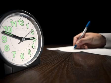 resolving: orologio con un uomo facendo prova scritta in background, low key, utile per application.education di lavoro e altri temi connessi test  Archivio Fotografico
