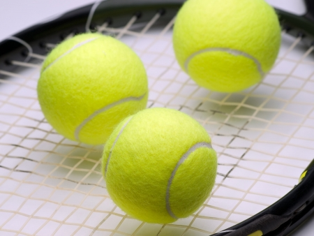 tennis balls on the racket ,for tennis,recreation and sport\ themes
