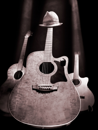 three acoustic guitars on the stage lit with the overhead lights , black and white photo, useful for music and entertainment themes Stock Photo