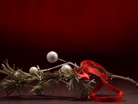 christmas branch decoration on the wooden surface with red background