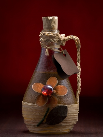decorative bottle of honey brandy ,on the wooden table and red background