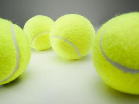 tennis balls on white surface ,selective focus on the ball in the middle,for various tennis,recreation and sport themes