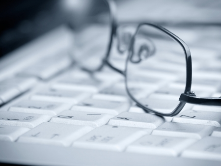 glasses on the computer keyboard ,closeup,selective focus and blue toned, for various office,research or computer themes Stock Photo