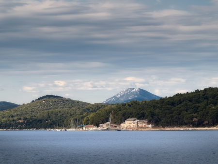 Adriatic coast with few old houses and with Osorscica hill in the background, town Mali Losinj,Croatia,Europe