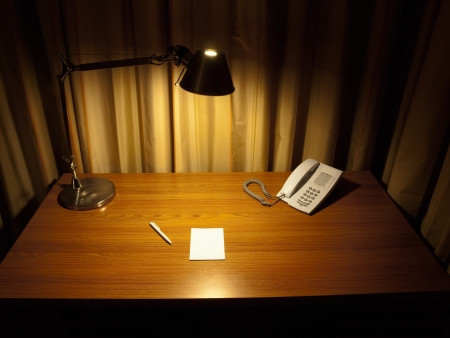 Room desk with the blank white paper,telephone and pen , lit by the lamp at night