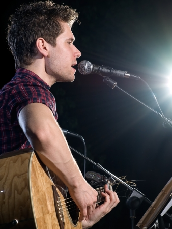 young musician playing acoustic guitar and singing, concert photo, for music and entertainment themes photo