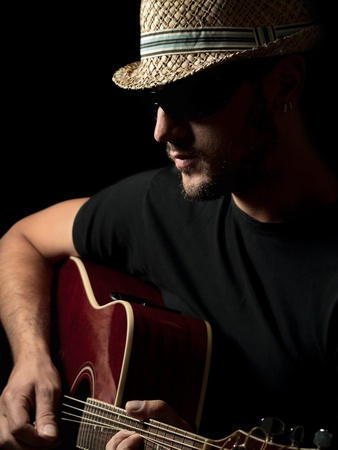 male musician wearing hat playing acoustic guitar, for concert and entertainment themes Stock Photo
