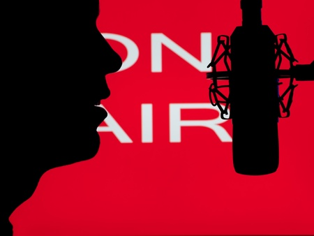 radio microphone: man speaking into the microphone with on the air sign in the background,for entertainment,broadcasting,sound themes