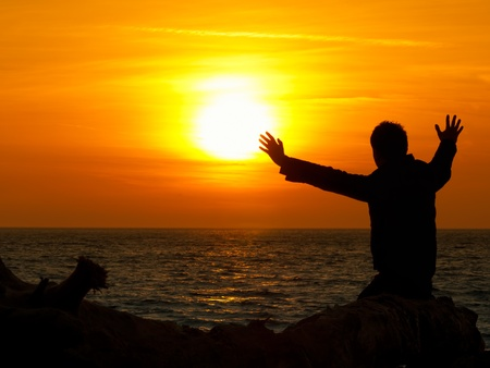 man sitting  by the sea with his arms raised to the Sun, sunset scene, for meditation,energy,freedom themes Stock Photo