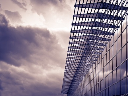 office building exterior: Modern glass building on the cloudy weather, toned image, for architecture,business,construction,real estate themes Stock Photo
