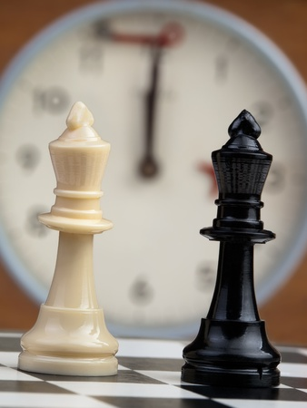 White and black king on the chessboard opposing eachother,old chess clock in the background,can be used as concept for conflict,meeting,agreement.. Stock Photo