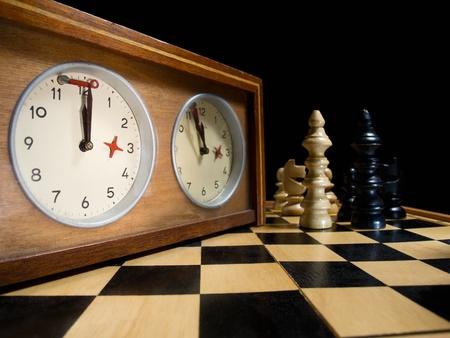 tablero de ajedrez: viejo reloj de ajedrez en el tablero de ajedrez con figuras, la bandera en la posici�n que indica que est� acabando el tiempo