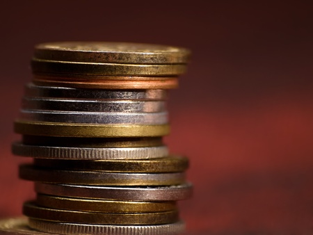 stack of coins against red background, closeup with shallow DOF photo