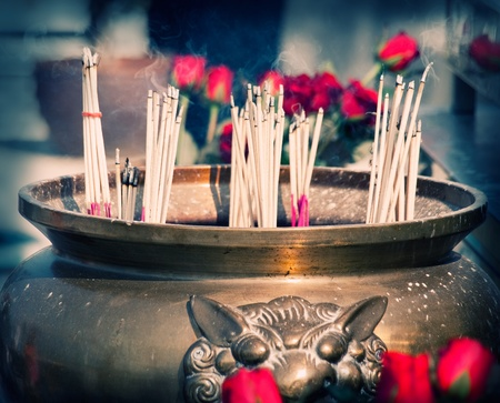 Buddhist shrine with smoking incense sticks and roses, cross-processed image , closeup