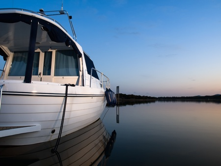 calm scenery of a boat docked in the bay at the sunset