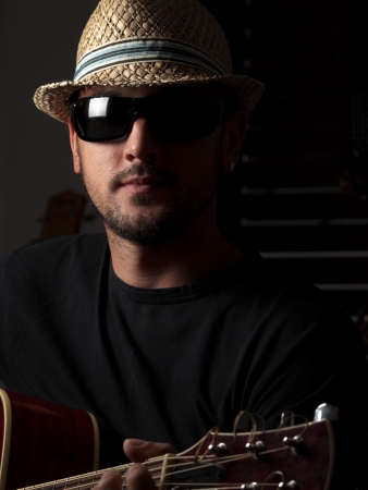 Young man with  hat and  sunglasses playing guitar, for entertainment,music themes 版權商用圖片