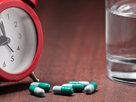Pills , clock and glass of water on the night table,closeup, for health care,medicine,drug themes Stock Photo