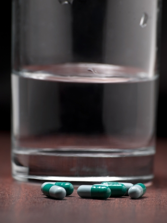 Pills on the night table with glass of water in the background,for medicine,health,addiction themes