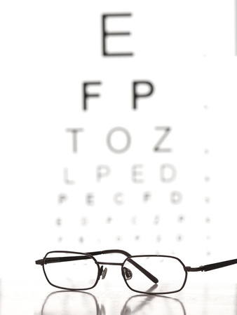 nearsighted: Glasses on the table with eye test chart in the background,for Distance Vision Test themes Stock Photo