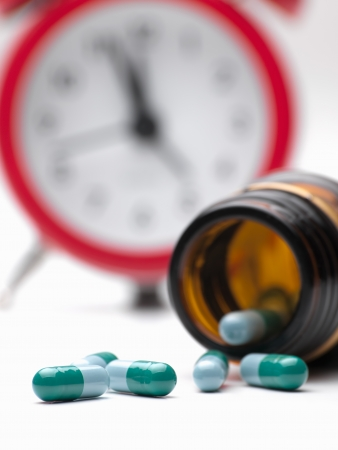 Pills  and clock  over white background,closeup, for healthcare,medicine,addiction themes