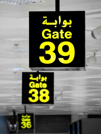 Gate signs in the airport building written in arabic language photo
