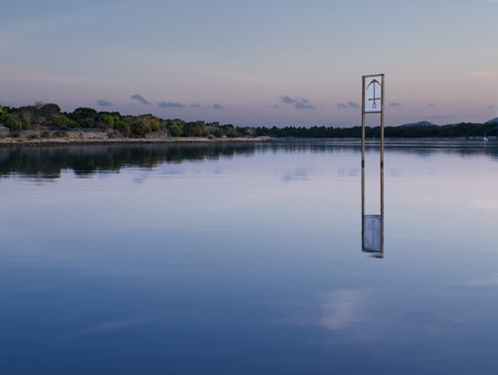 Bay with the anchor sign-board in the shallow water , peaceful scene in the sunset