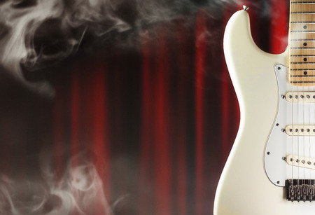 stratocaster: Electric guitar on the stage closeup with smoke and  red curtains, for music,entertainment themes
