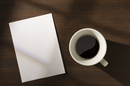 Blank paper note and coffee on the table