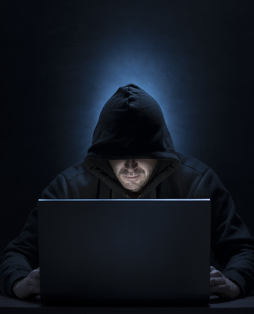 Hooded man on the computer, for hacking,spying,internet security themes 版權商用圖片 - 92401086