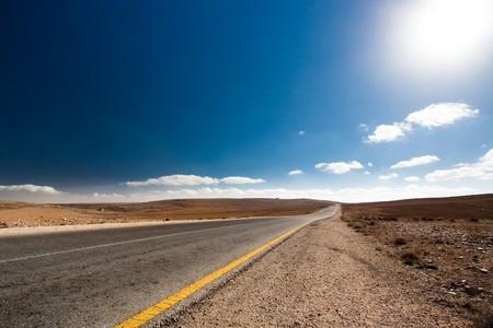 Strada senza automobili in Giordania nel deserto con tempo soleggiato.