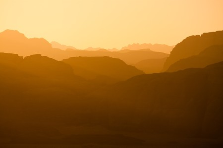 the setting sun: Distant mountains lit by the setting sun in the Wadi Rum desert reservation, Jordan. Stock Photo