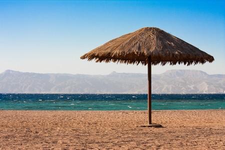 Unico ombrellone vicino la costa del mare lettura di Aqaba, in Giordania.