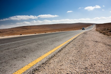 Anonymous car driving toward the viewer on a desert road. Stock Photo
