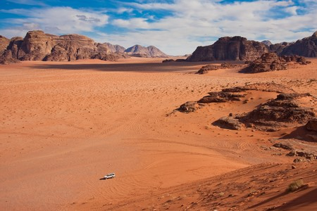 Small car in a huge desert of Wadi Rum. Shot from the only massive sand dune. Stock Photo