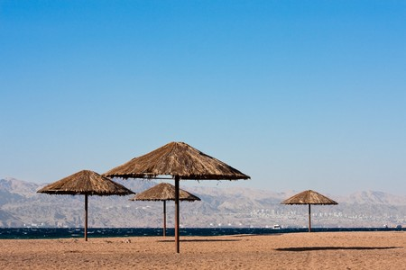 Sunshades near on beach of the Read Sea in Aqaba, Jordan. City of Eilat, Egypt in background. Stock Photo