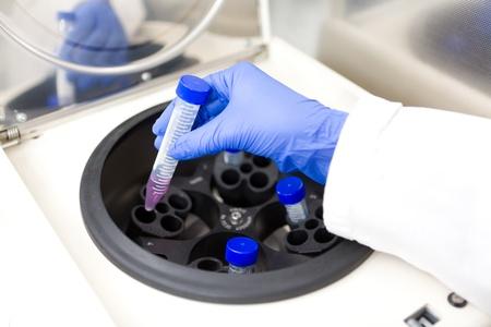 centrifuge: Scientist putting test tube into centrifuge