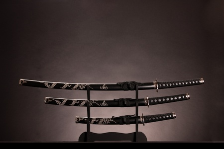 traditional weapon: Three ancient japanese swords with a monochrome lighting. Text can be inserted in the upper part of the image.