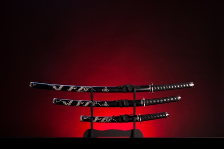 tsuka: Three ancient japanese swords with a dramatic lighting. Text can be inserted in the upper part of the image. Stock Photo