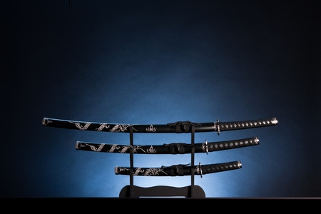 Three ancient japanese swords with a calm lighting. Text can be inserted in the upper part of the image. Stock Photo