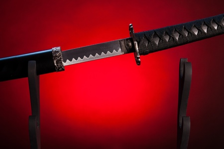 Long japanese sword with  a blade visible. The background is colored in red. photo