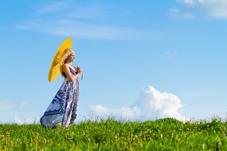 Ragazza con giallo in piedi lateralmente alla fotocamera, prato, in primavera. Copiare lo spazio. Archivio Fotografico