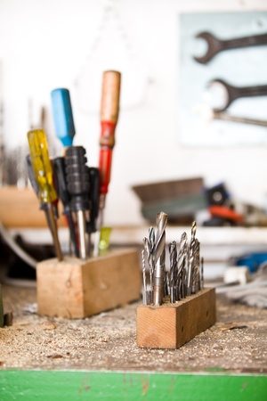 Focused drills with screwdrivers in background, workshop Stock Photo