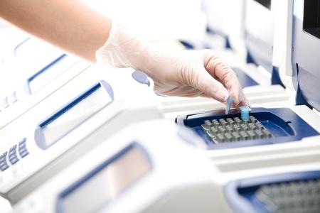 Scienziato, copia del DNA, Real-time PCR cycler, guanti bianchi, distante
