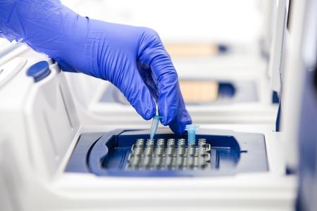 Scienziato con la copia del DNA, Real-time PCR cycler, girato nei pressi